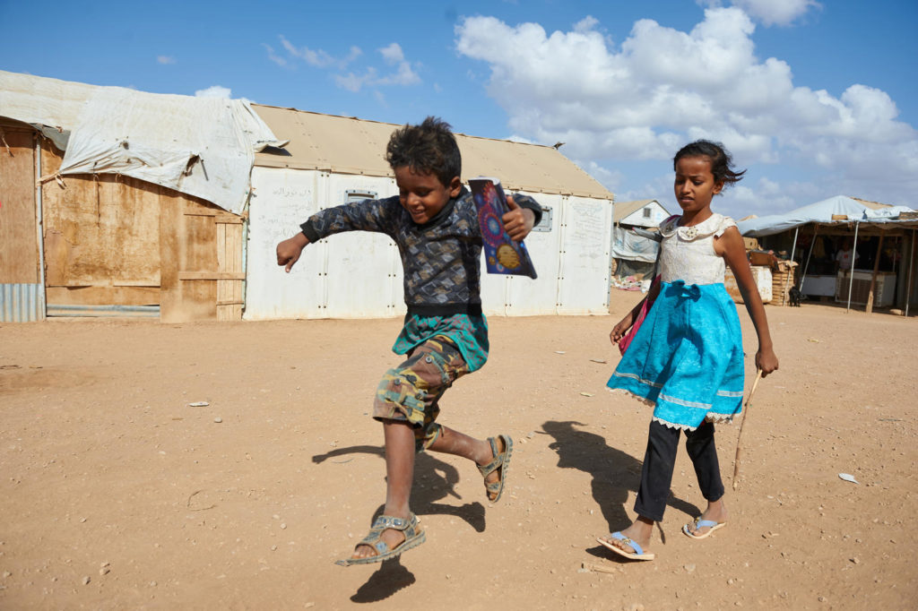 A boy and girl walking on a dirt path in between makeshift dwellings. The boy skips as he walks in front of the girl.