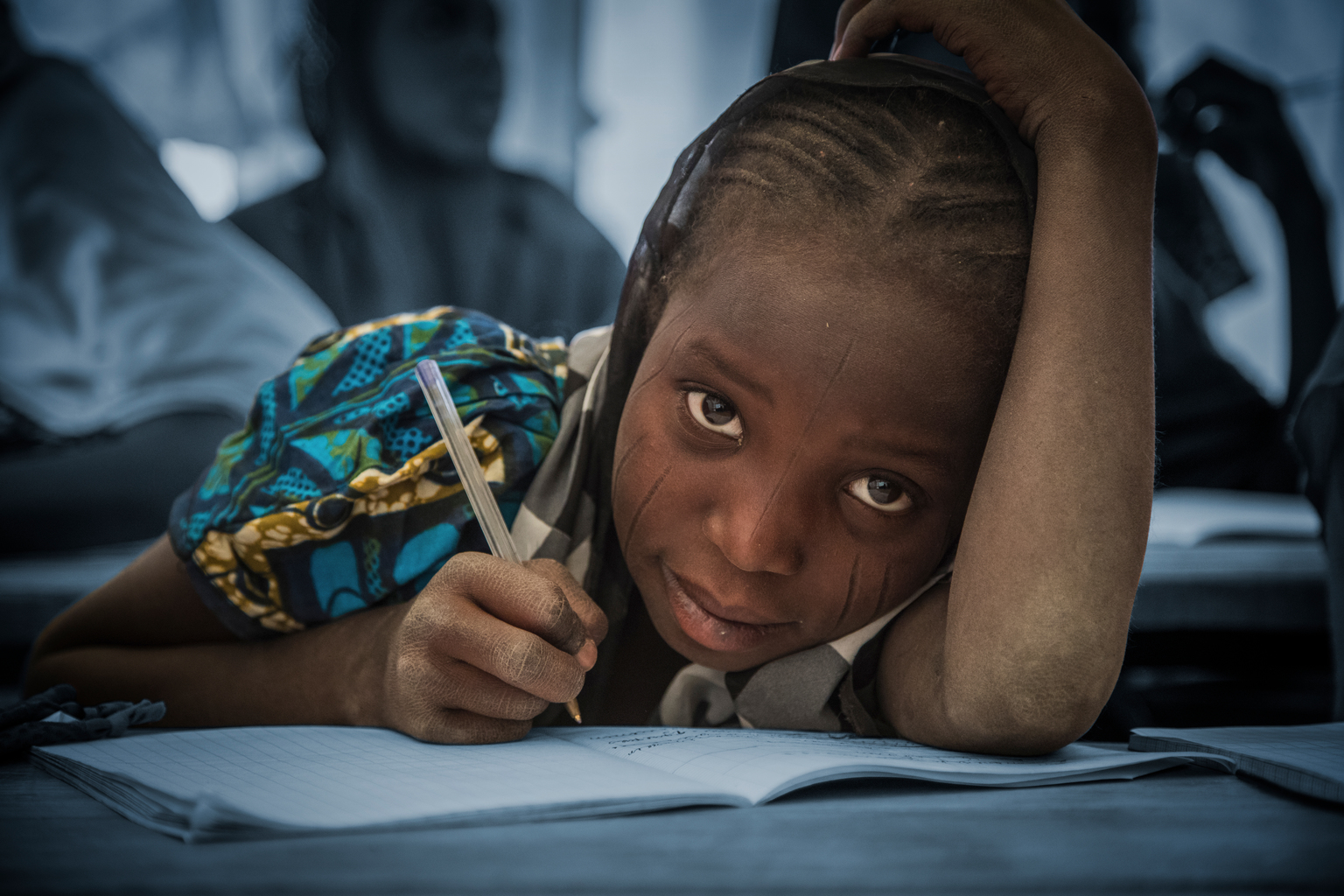 A young girl holding a pen rests her head and arm on the open notebook on the desk in front of her as she looks up.