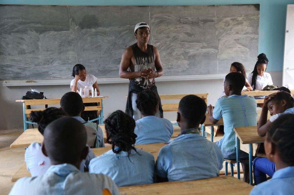 A young man in a black 'Nirvana' tank top and jeans addresses a classroom of students in blue school uniform.