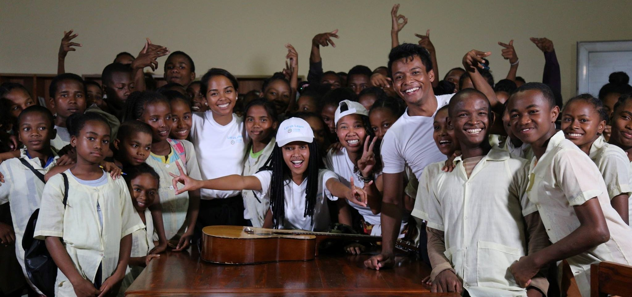 A group of school children cheering standing around a table with a guitar on it.