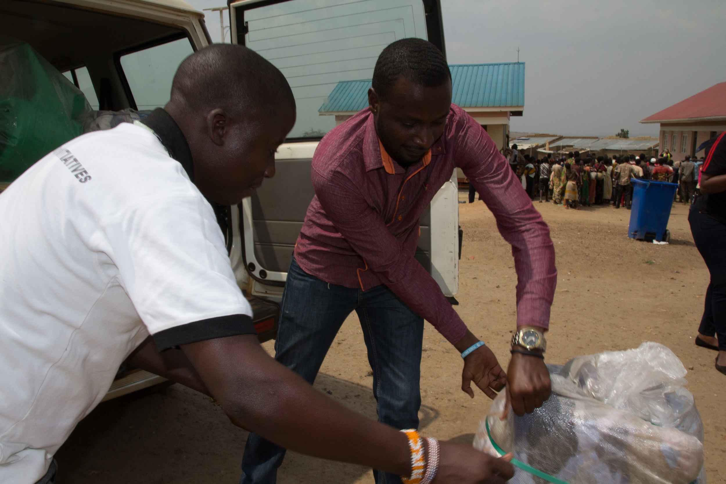 Two men pulling out a sack of supplies from the back of a truck putting it on the ground