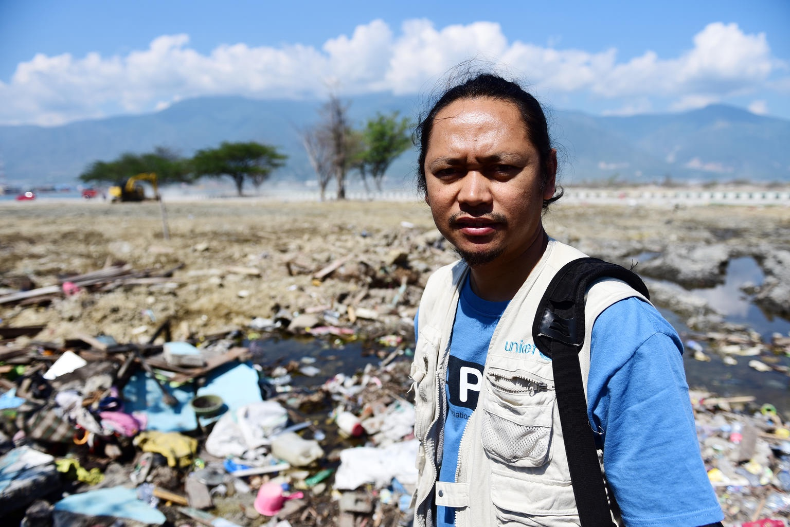 A health worker in a context of rubble and a blue sky in the distance.
