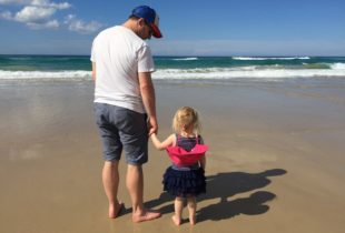 A man holding a little girl's hands at the beach.