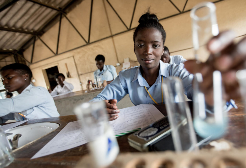A schoolgirl sitting at a table with an open school workbook in front of her picking up an empty test tube.