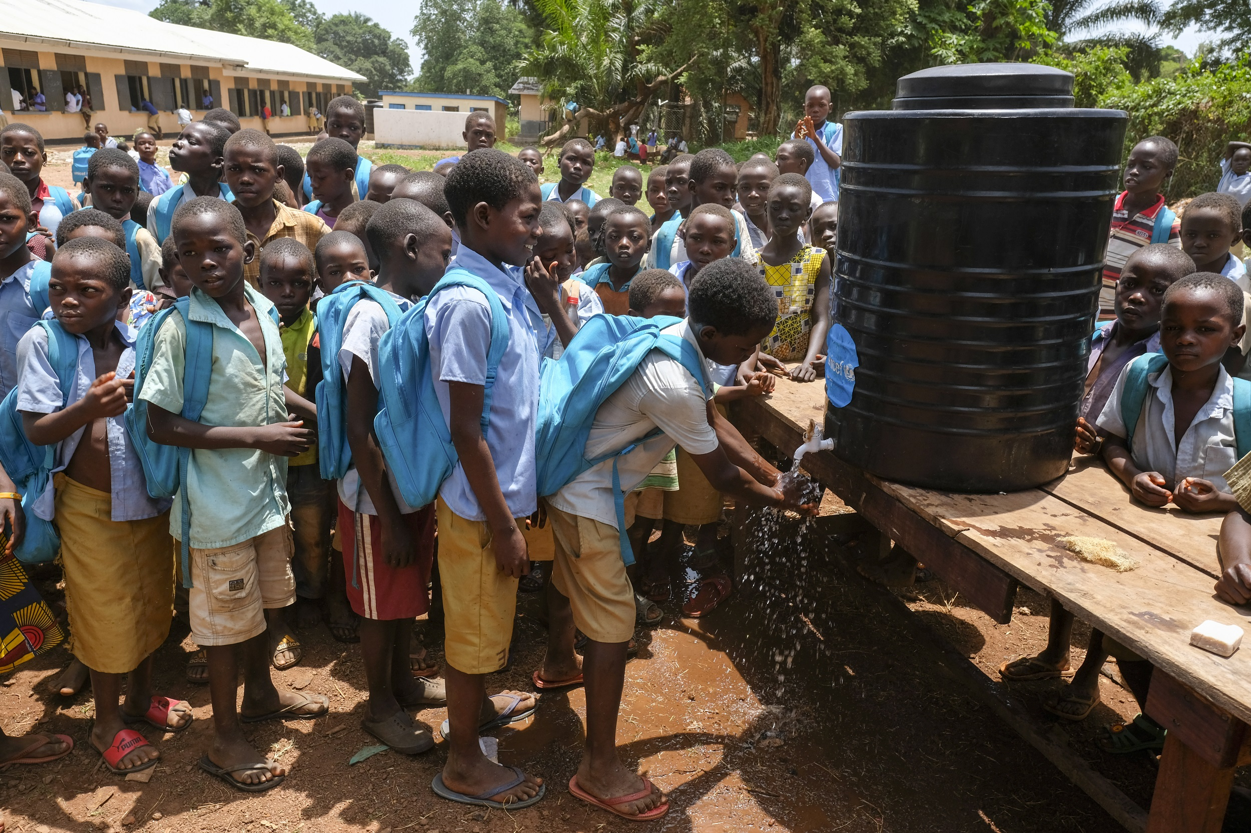 School children line behind one another. The child at the head of the line washes his hands at a tap attached to a large black plastic container.