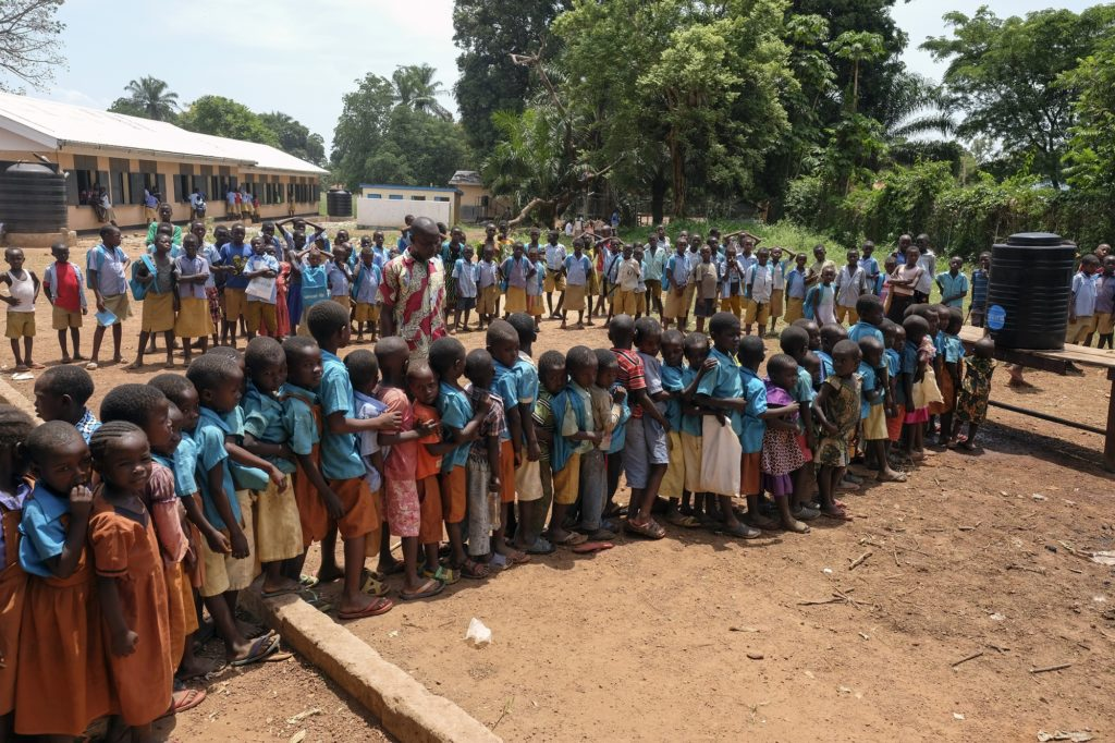 School children lined up in front of a black plastic water container.