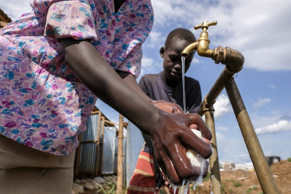 A young girl looks on as an adult washes hands with soap under a running brass tap.