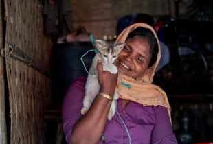 A smiling woman holds up a cat in her arms.