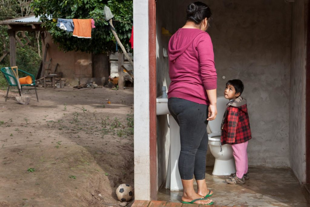 A lady looks at a little boy looking up at her from the toilet in an outdoor shed.