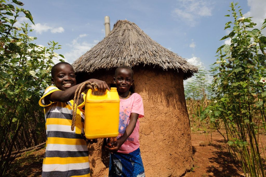 Two children outside a thatched-roof hut display the yellow jerrycan of water they are holding.