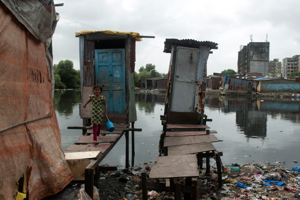 A young girl walks out of one of two small makeshift wooden cabins on stilts and overlooking a large drain.