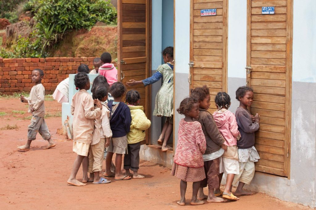 Two queues of children await their turn outside three outdoor wooden bathroom doors.