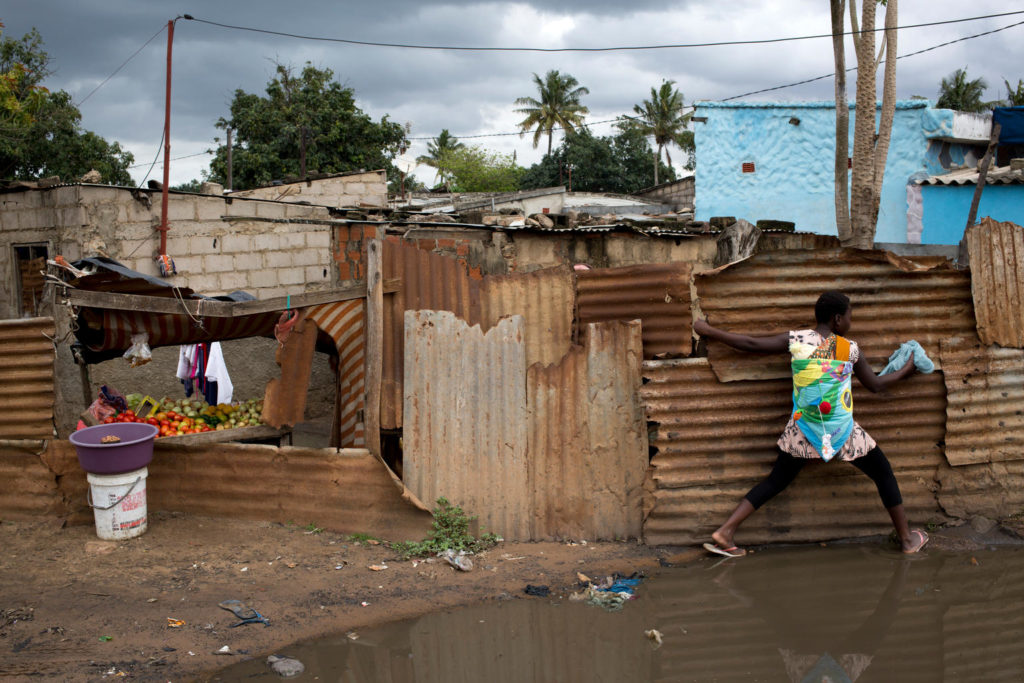 A young lady jumps across a large muddy puddle of water as she uses a fence of corrugated iron as support.