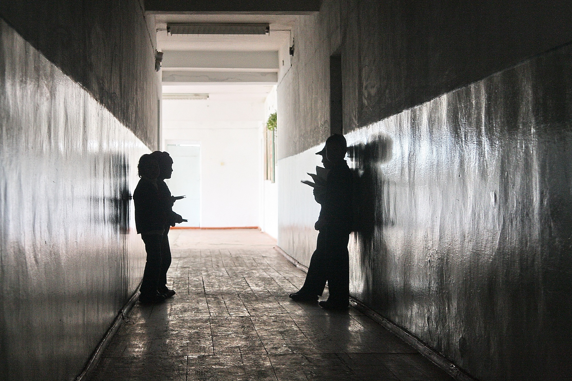 Some children in silhouette on either side of a dark passageway.