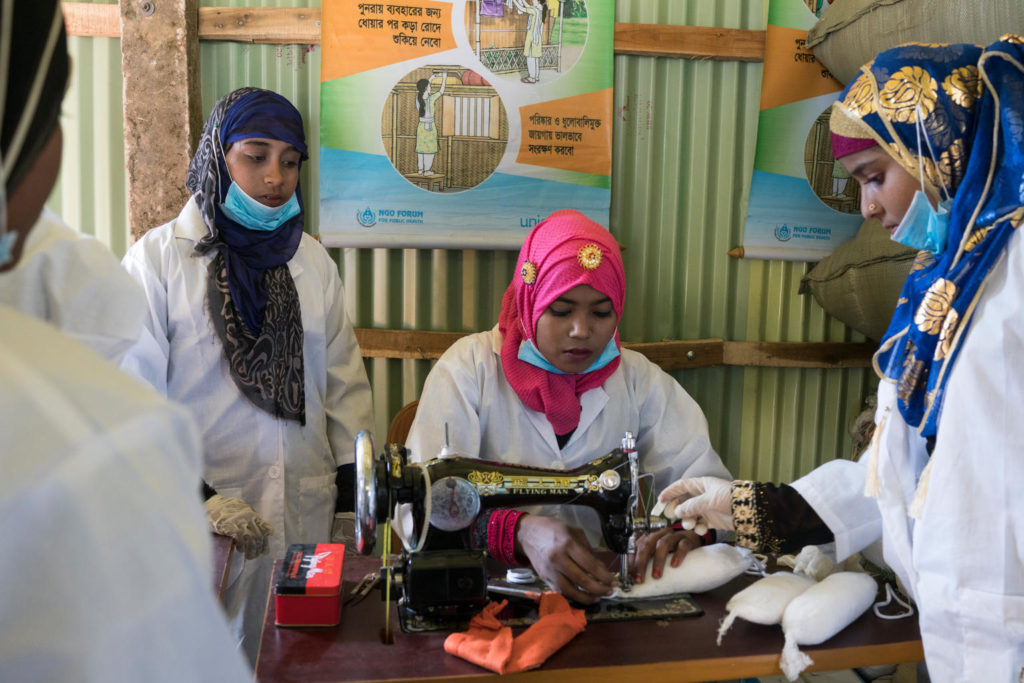 A lady in a white coat and traditional headscarf is working on a sewing machine as two other ladies look on.