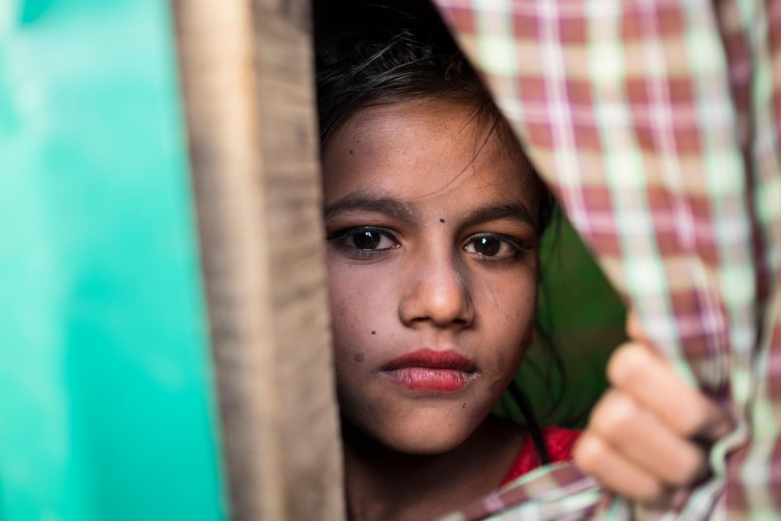 A young lady peers through from behind a curtain she has held open.