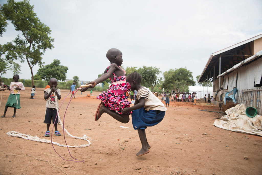Two girls in mid-air as they skip-rope together as a young boy looks on.