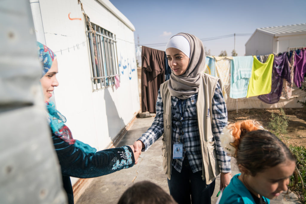 A young lady greets another lady by shaking hands at the door of a house while children play in the foreground.