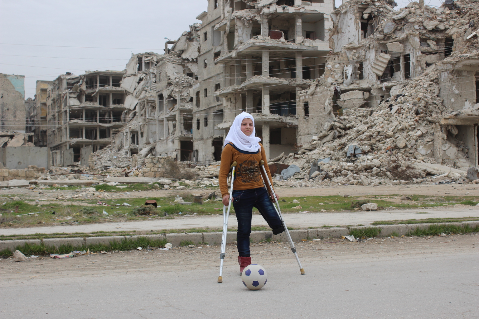 A girl with only one leg stands on crutches in front of a bombed out building