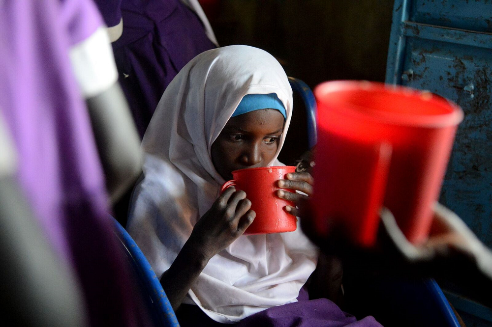 A young girl in a white head scarf drinks from a red plastic mug