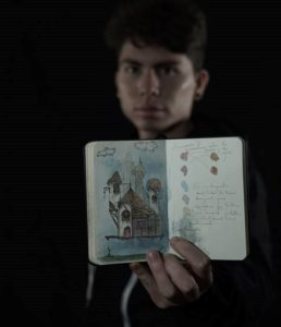 A portrait of a boy holding up a tiny notebook of illustrations