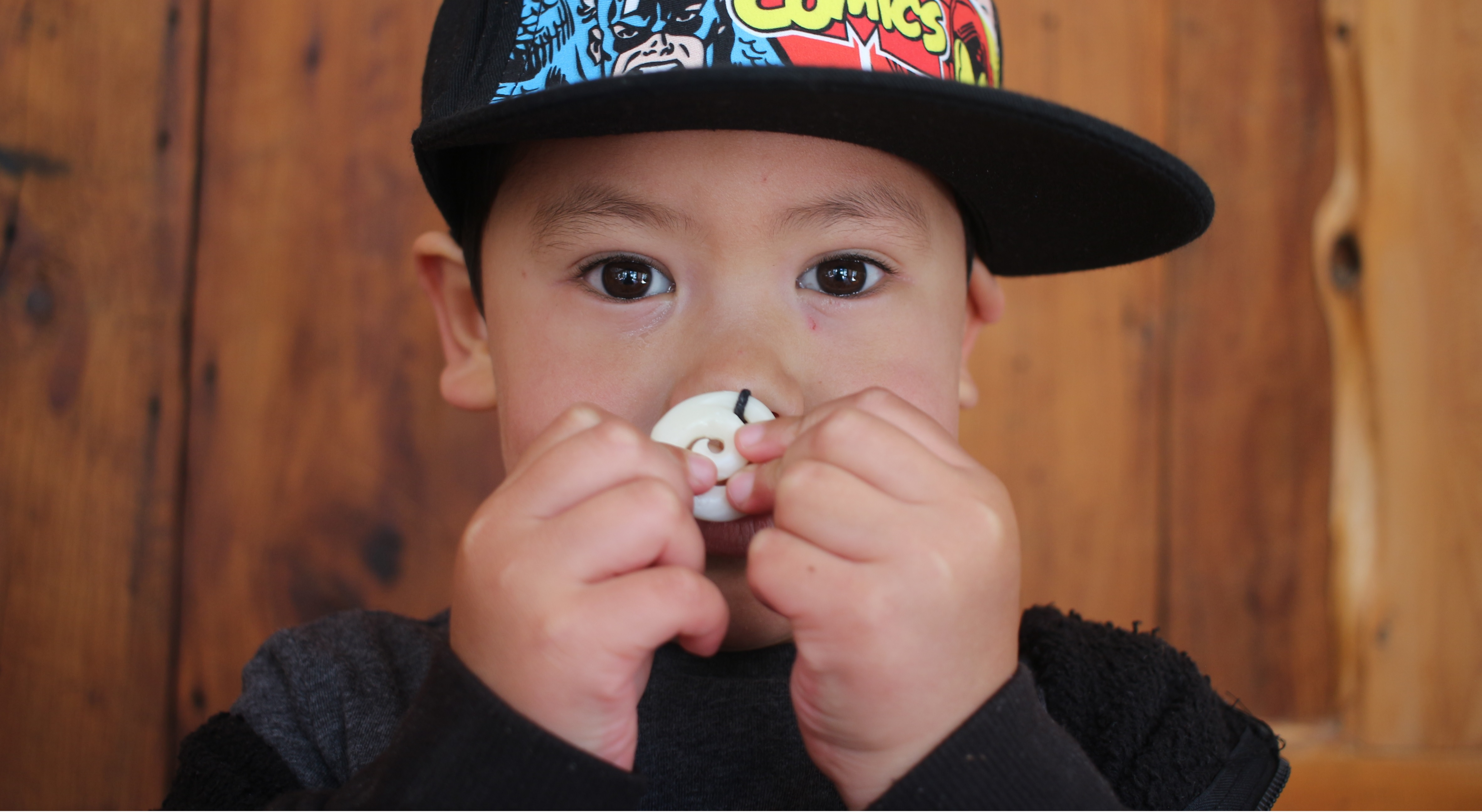 A young child holding a small circular white object close to his face