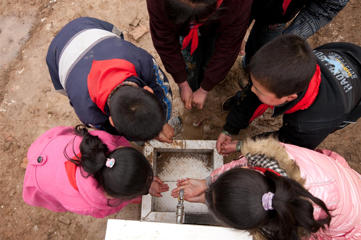 Top view of some young boys and girls using an outdoor water tap.