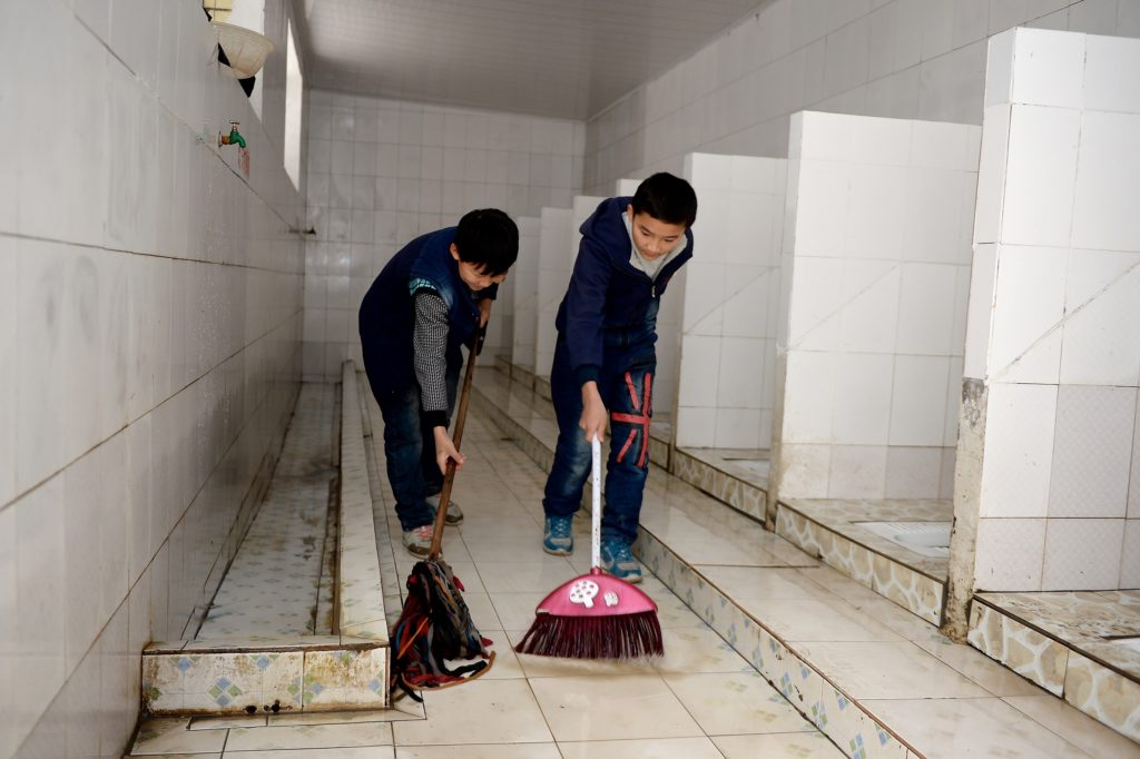 Two young boys are bent over mopping a toilet floor.