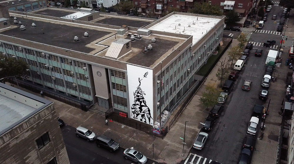 Aerial view of the corner of a building that features a large hand-painted mural across a section of the wall.