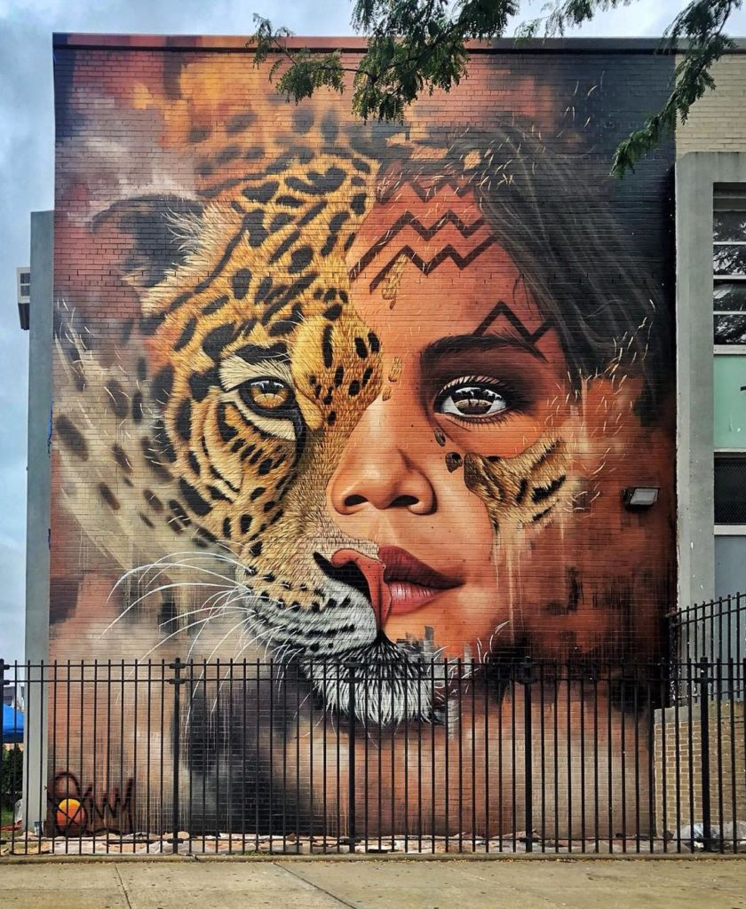 A hand painted mural on a large wall depicting a child's face blended with that of a tiger.