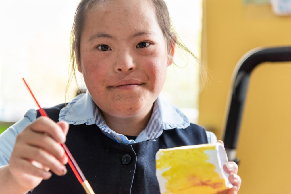 A girl in school uniform holding a paint brush and a paint can