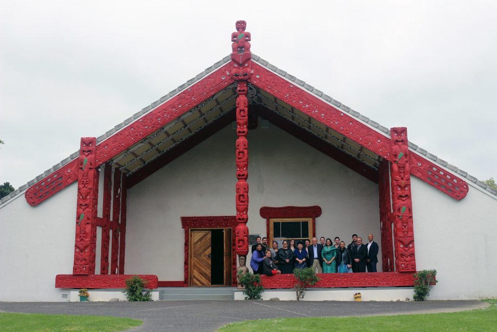 A group of people stand huddled together under the high roof of a large wooden hut painted white and red.