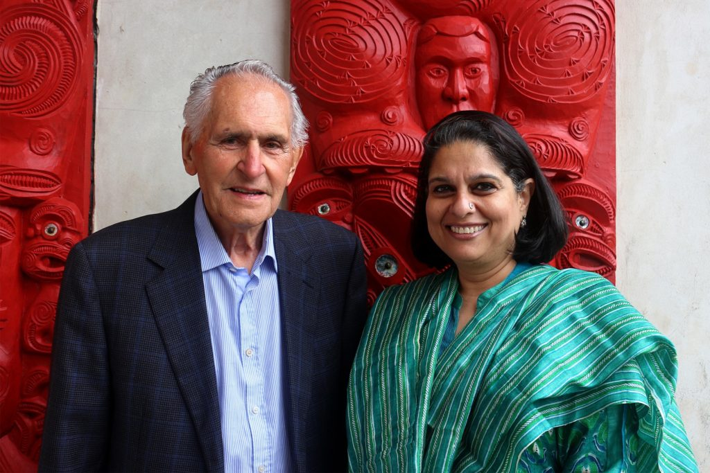 An elderly gentleman and a lady stand together with a red back drop behind them.