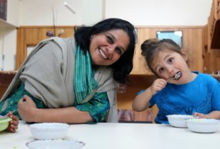 A lady leans in sitting beside a child with a spoon in her mouth.
