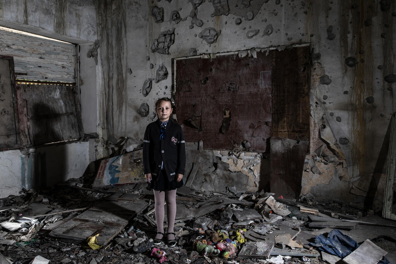 A young girl stands in a room that is now largely rubble.