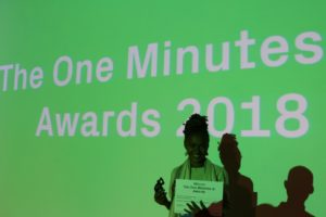A young girl stands in front of a video screen holding an award.