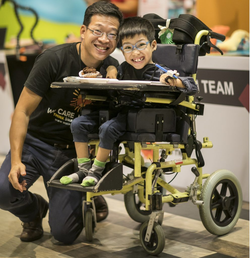 A smiling boy in a wheelchair, with his dad beside, and the invention he's made.