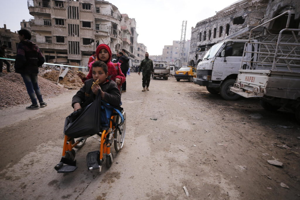 A child pushes another on a wheelchair amidst the rubble of a destroyed city.