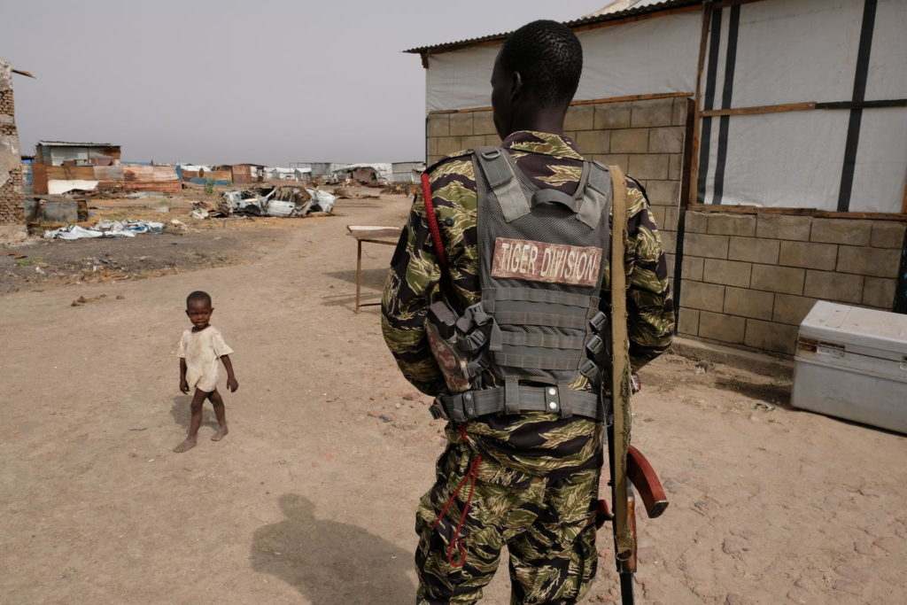 An armed soldier with a vest bearing the words 'Tiger Division' looks on as a child walks by.