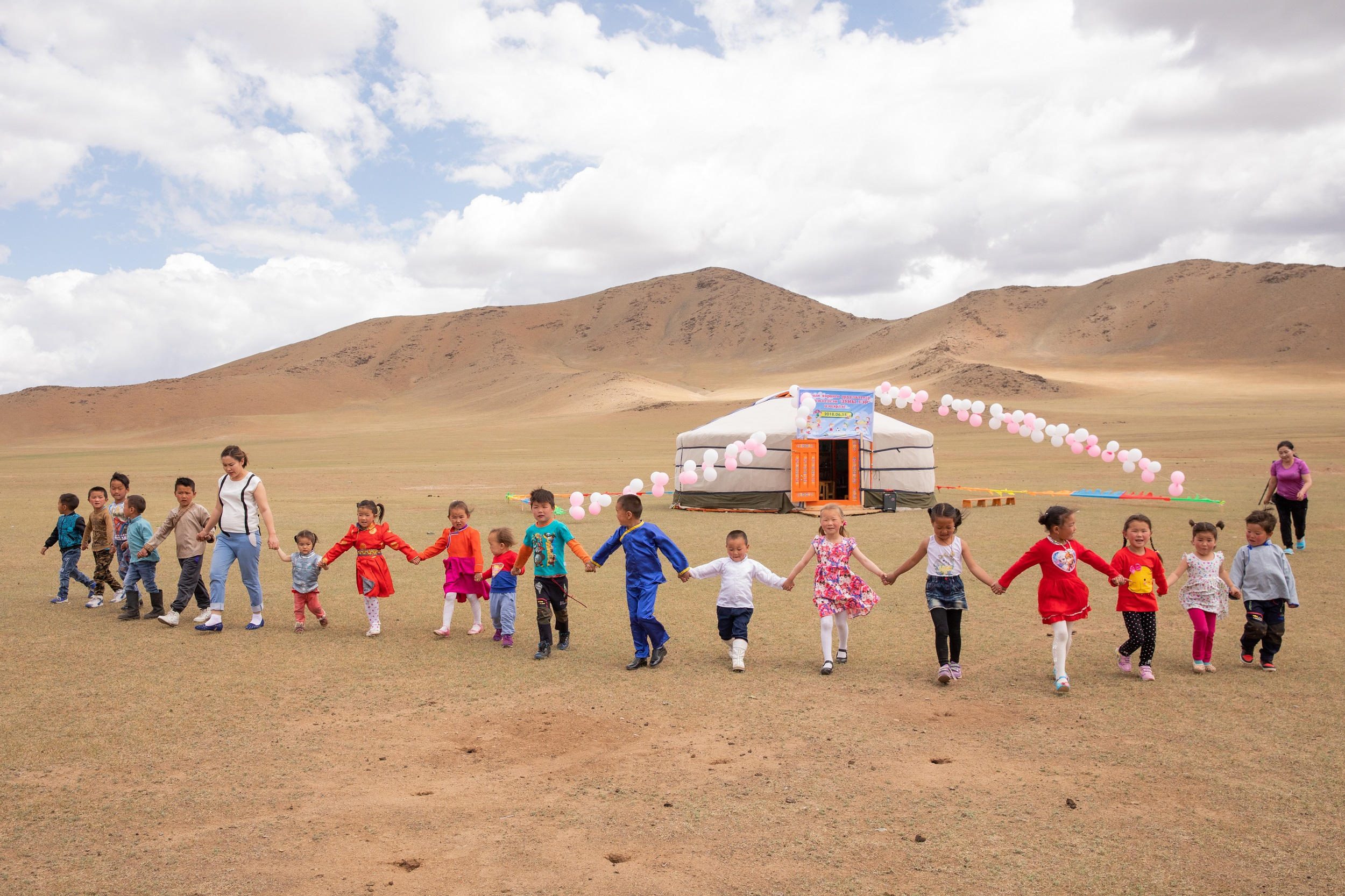 A group of children holding hands creating a human chain walking towards us.