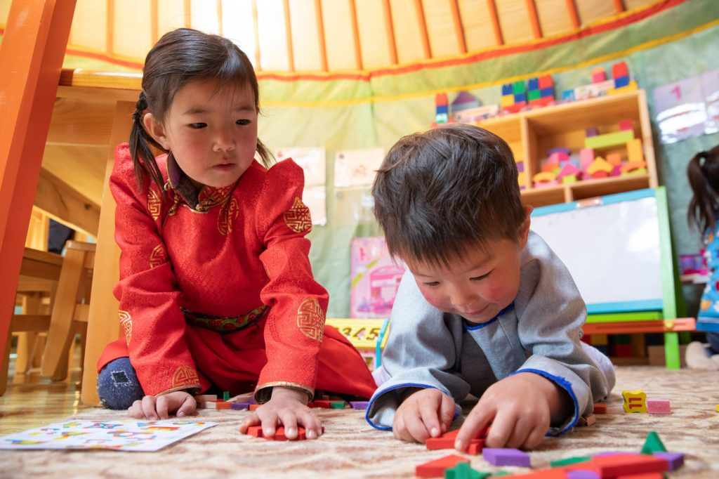 A small boy plays with building blocks on the floor as a small girl beside him in a traditional red dress looks on.