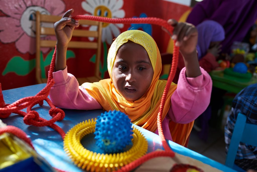 A young girl holds up a red rope above her head as she looks at other toys on the table in front of her.