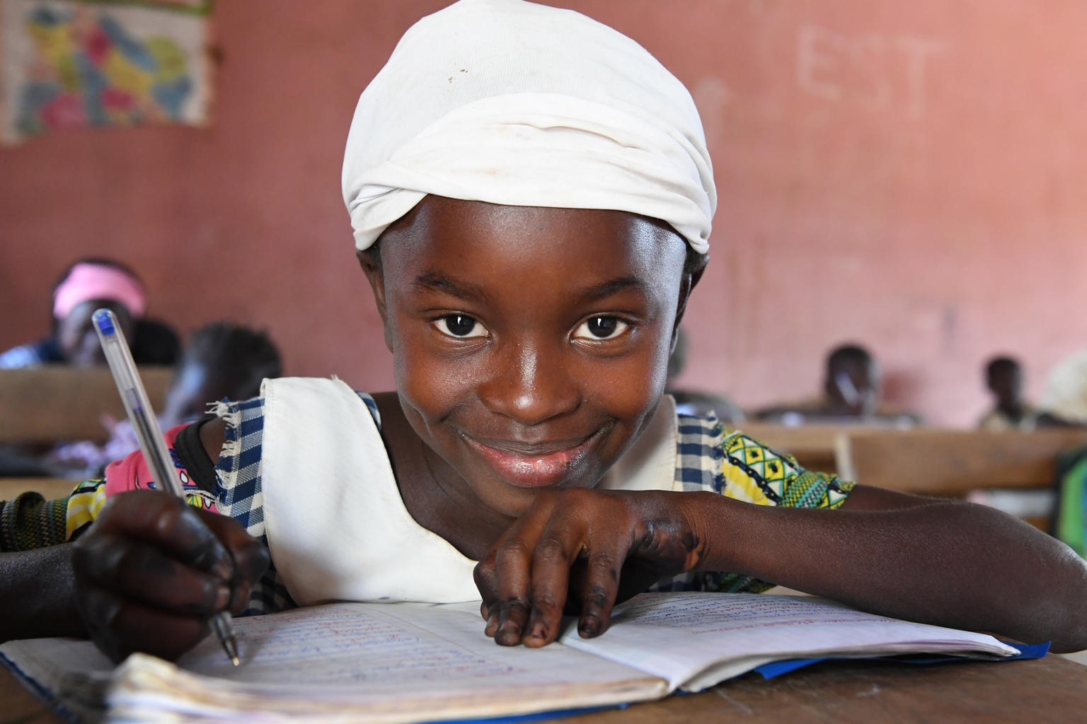 A smiling girl writes with a pen in a notebook.