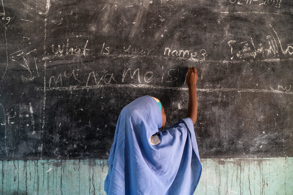A young child in traditional clothing writes with the help of chalk on a blackboard.