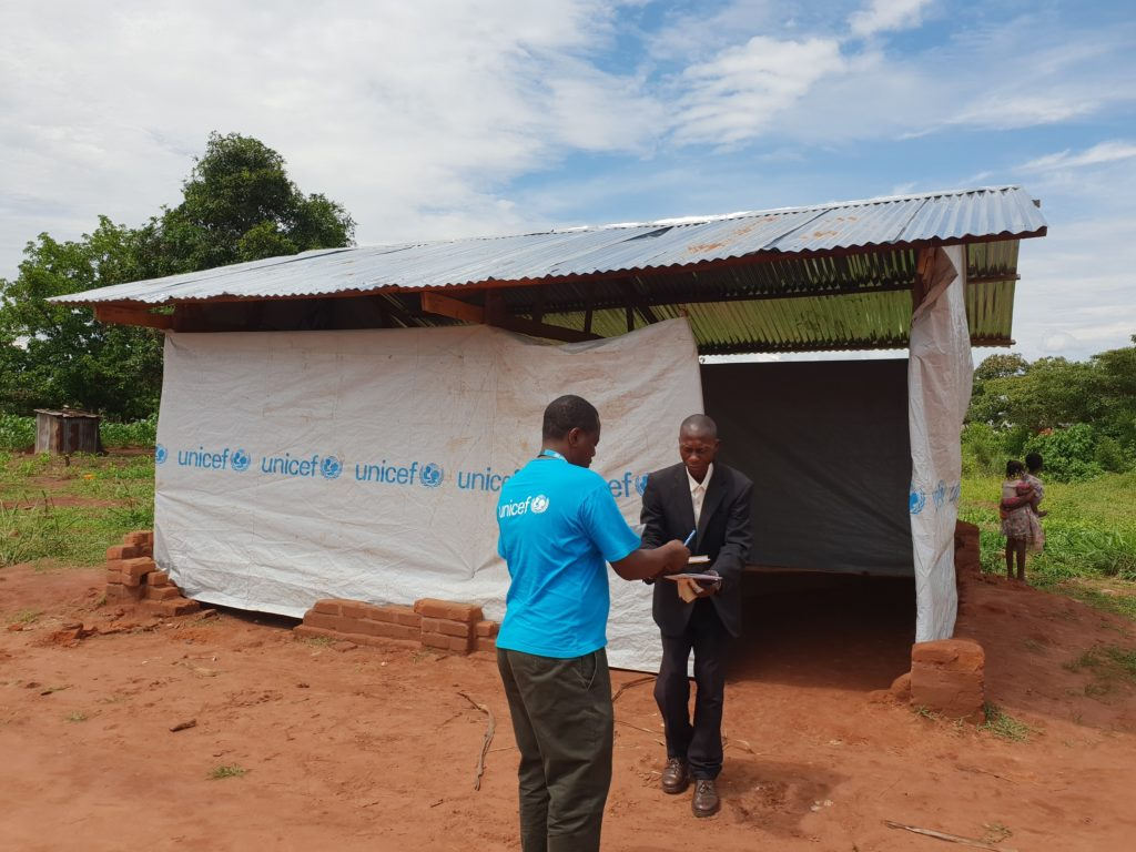 A man in a black suit outside a shed clad in UNICEF-marked tarp holds out a book to another man in a UNICEF vest holding a blue pen.
