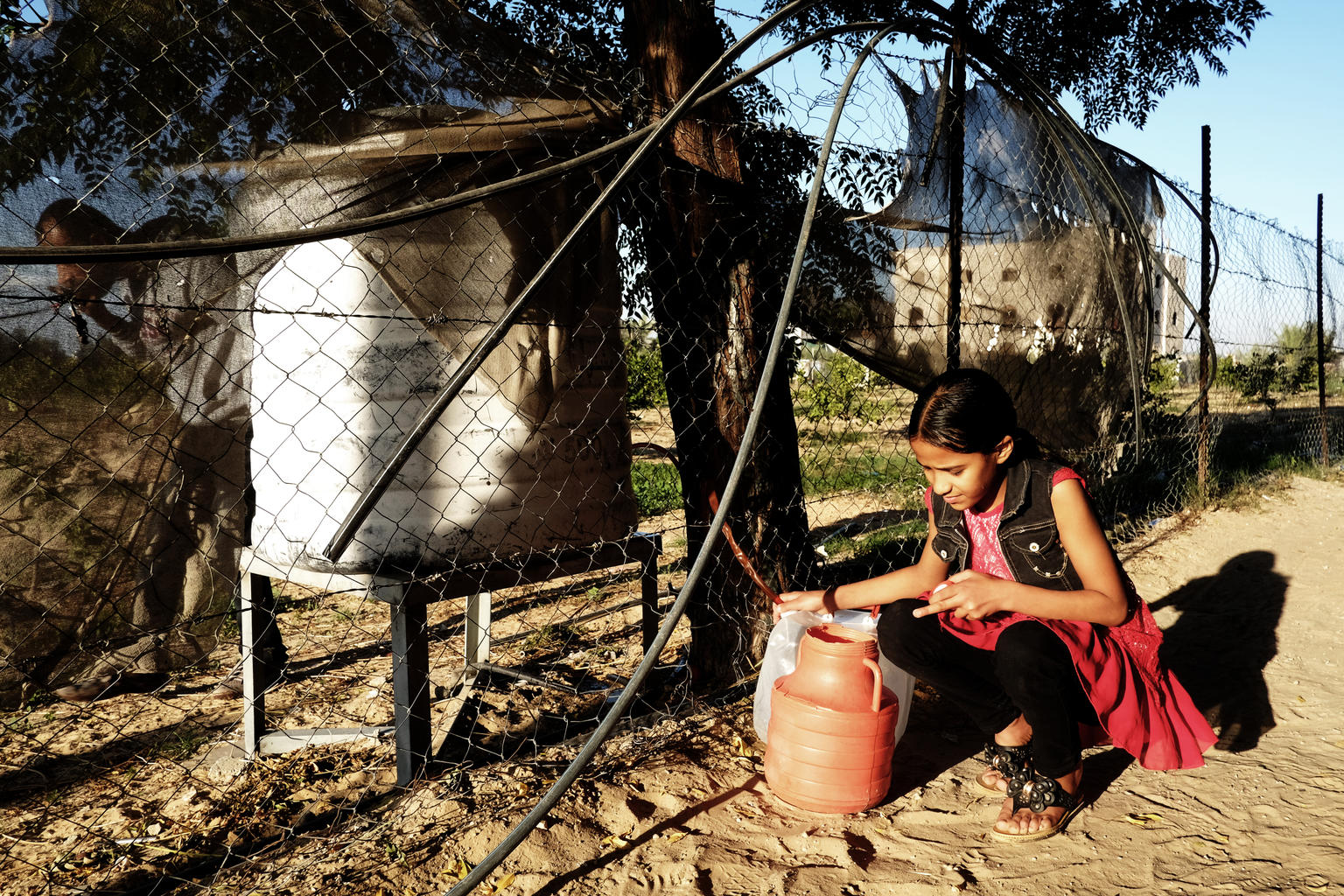 A young lady squatting on the ground as she uses a hose to fill water into two jerrycans.
