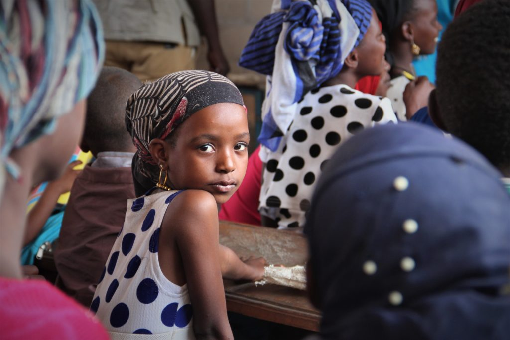 A young girl sitting among a group of women in a classroom turns back to look at us.