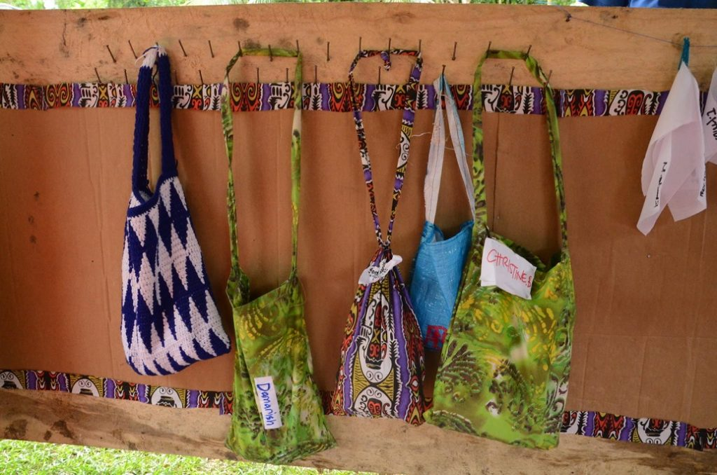 A series of colorful cloth bags hanging on low hooks.