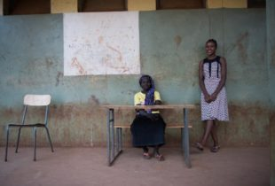 Two girls in an empty classroom, one of them sitting behind a desk while the other stands beside against the wall.