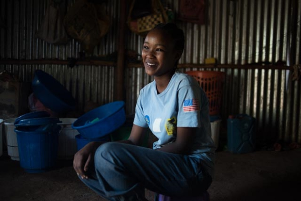 A girl wearing jeans and a blue t-shirt sits smiling inside a shanty.